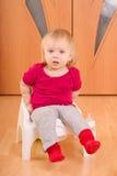 O bebê senta-se no toalete da cadeira Fotos de Stock
