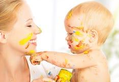 O bebê sujo feliz tira pinturas em sua cara da mãe