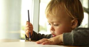 O bebê tira com um lápis vídeos de arquivo