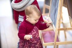 O bebê tira o giz no quadro-negro na compra da área das crianças imagens de stock royalty free