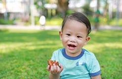 O beb? asi?tico feliz aprecia comer o frango frito no jardim verde exterior fotografia de stock