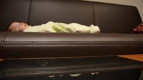 O beb? de limpeza do whille da tabela do coffe da m?e est? dormindo no sof?