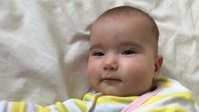 O bebê pequeno encontra-se e torce-se sua cabeça no movimento lento vídeos de arquivo
