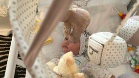 O bebê pequeno está encontrando-se na cama e está olhando-se o sobre os brinquedos de giro filme
