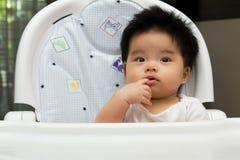 O bebê pequeno senta-se em uma cadeira elevada Foto de Stock Royalty Free