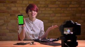O beleza-blogger fêmea de cabelos curtos que mostra interessantemente a tela verde do smartphone na câmera bricken sobre a parede filme