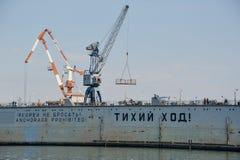 O beliche da carga nos guindastes do rio e de torre no porto Fotografia de Stock