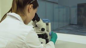 O biólogo fêmea olha em um microscópio video estoque