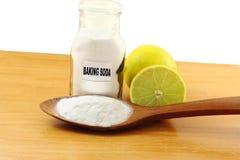 O bicarbonato de sódio na garrafa de vidro e a colher de madeira com limão frutificam Fotos de Stock Royalty Free