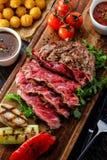 O bife de vaca grelhado cortado raro suculento serviu com tomates e foto de stock