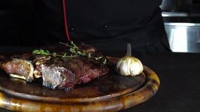 O bife fritado na grade encontra-se em uma placa de madeira com vegetais filme