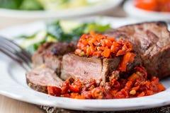 O bife grelhado com molho da salsa secou tomates, pimentas vermelhas Fotos de Stock Royalty Free