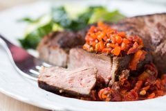 O bife grelhado com molho da salsa secou tomates, pimentas vermelhas Foto de Stock Royalty Free