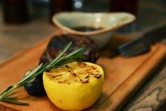 O bife grelhado e a metade brindaram o limão em uma placa de madeira Foto de Stock