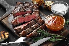 O bife raro médio grelhado cortado serviu no assado da placa de madeira, lombinho de carne da carne do BBQ fotos de stock royalty free