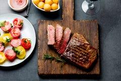 O bife raro médio grelhado cortado serviu no assado da placa de madeira, lombinho de carne da carne do BBQ Vista superior, fundo  fotografia de stock royalty free