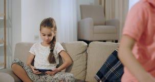 O big brother e a irmã pequena têm um momento junto após a escola que toma se senta no sofá e se toma um smartphone para joga vídeos de arquivo