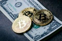 O bitcoin dourado inventa em um dinheiro de papel dos dólares e em um fundo escuro com sol Moeda virtual Moeda cripto dinheiro vi fotografia de stock