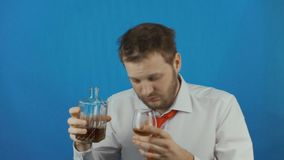 O biusinessman bêbado não barbeado desconcerta e bebe o rum ou o uísque ou a aguardente ou o conhaque vídeos de arquivo