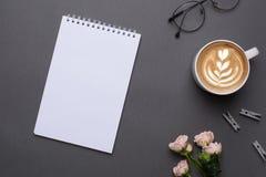 O bloco de notas branco com café e as flores no fundo cinzento no vintage denominam a vista superior fotografia de stock