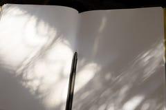Caderno branco e pena preta na luz solar Foto de Stock