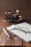 O bloco de notas com pena e os vidros não se encontram tabela de madeira, e ao lado de uma xícara de café Imagens de Stock