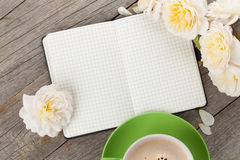 O bloco de notas, o copo de café e a rosa vazios do branco florescem imagens de stock