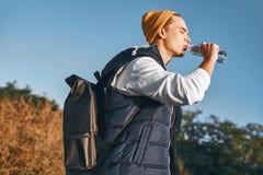 O blogger à moda novo do turista é água potável ao andar nas montanhas fotos de stock royalty free