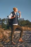 O blogger à moda novo do turista é água potável ao andar nas montanhas foto de stock royalty free