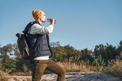 O blogger à moda novo do turista é água potável ao andar nas montanhas imagens de stock