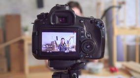 O blogger bonito novo da mulher DIY escreve o vídeo na oficina da garagem usando a ferramenta video estoque