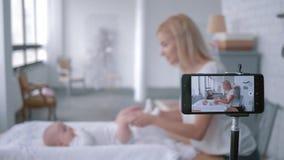 O blogger da mamã faz a ginástica para sua pouca filha na tabela em mudança e registros video para subscritores em social video estoque