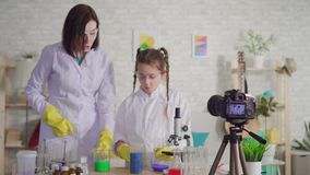 O blogger da mulher e do adolescente, mistura os reagentes em um laboratório químico video estoque