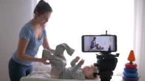 O blogger do trabalho, vlogger novo da mamã muda a roupa do menino da criança ao gravar o vídeo da educação no smartphone para video estoque