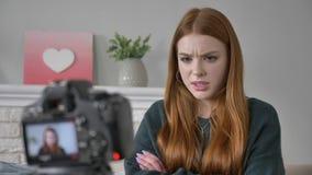 O blogger ruivo bonito novo da menina fala na frente da câmera, mostra uma emoção do descontentamento, conforto home dentro filme
