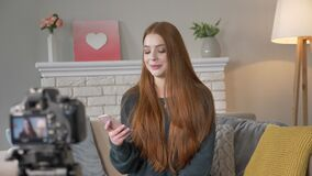 O blogger ruivo novo da menina, fala de sorriso na câmera, usando o smartphone gesticula com mãos, conforto home no vídeos de arquivo