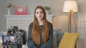 O blogger triste triste vermelho novo da menina fala na câmera, gestos com mãos, homeliness no fundo 60 fps video estoque