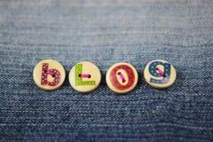 O blogue da palavra soletrou em botões indicados por letras na sarja de Nimes Fotos de Stock Royalty Free