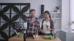 O blogue do emagrecimento, o homem dos vloggers e a fêmea prepararem a refeição matinal saudável com vegetais e os verdes na culi filme