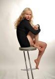 O Blonde é assento na cadeira Fotografia de Stock Royalty Free
