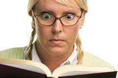 O Blonde chocado com Ponytails lê um livro foto de stock