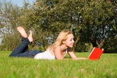 O Blonde lê o livro no parque Fotos de Stock Royalty Free