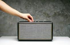 O bluetooth do orador da abertura da mão na tabela branca imagens de stock