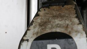 O bocal de combustível oxidado dilapidado velho no posto de gasolina pendura perto acima da vista filme