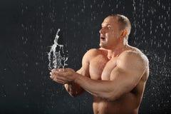 O Bodybuilder na chuva joga a água nas mãos Foto de Stock Royalty Free