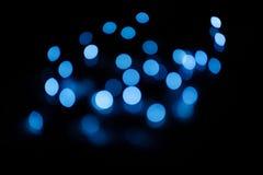 O bokeh azul circunda em um fundo escuro, abstração, fundo imagens de stock