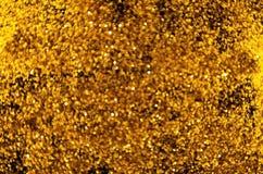 O bokeh obscuro pequeno dourado circunda no fundo escuro fotografia de stock