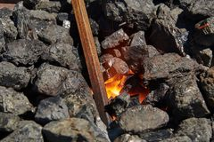 O boleto do metal é caloroso em carvões ardentes foto de stock royalty free