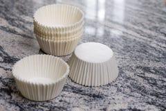 O bolo branco vazio do copo encaixota recipientes no fundo cinzento do mármore do granito Foto de Stock