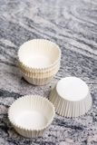 O bolo branco vazio do copo encaixota recipientes no fundo cinzento do mármore do granito Fotografia de Stock Royalty Free